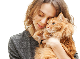 Woman nuzzling with orange cat