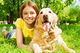 Young girl laying on grass with golden retriever