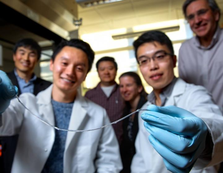 Diabetes researchers from across Cornell hold a sample of their therapy device
