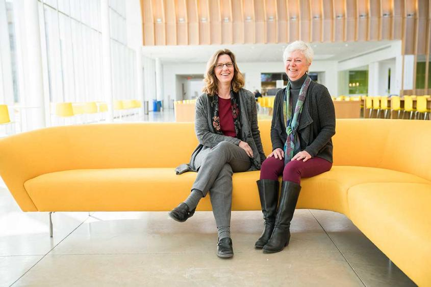 Jodi Korich and Julie Powell sitting on a couch in the Schurman atrium