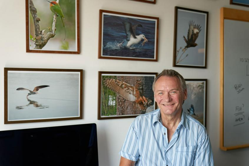 David Russell stands in front of a wall of his wildlife photographs
